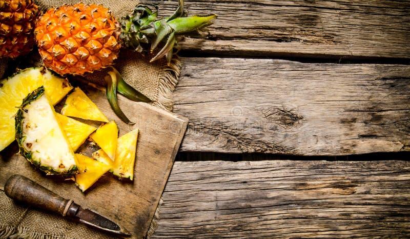 Skivad ny ananas med en kniv på en skärbräda royaltyfria foton