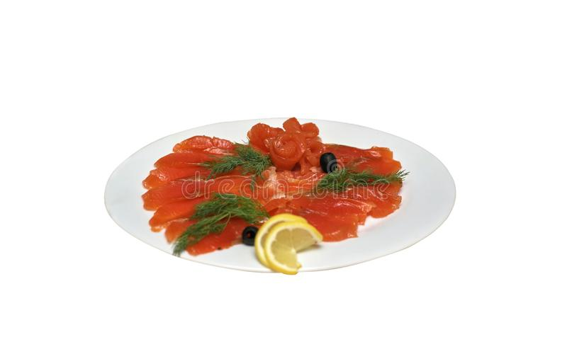 Skivad röd fisk med oliv och citronen på en vit platta, isolat arkivbild