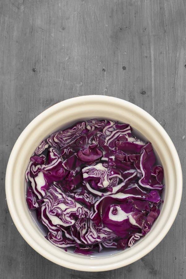 Skivad rödkål i vatten i en keramisk skål fotografering för bildbyråer