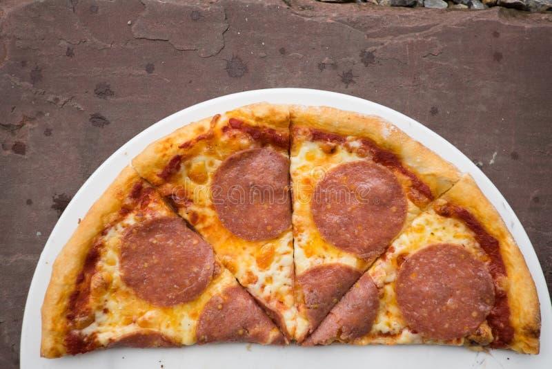 Skivad salamipizza på en vit platta royaltyfria bilder