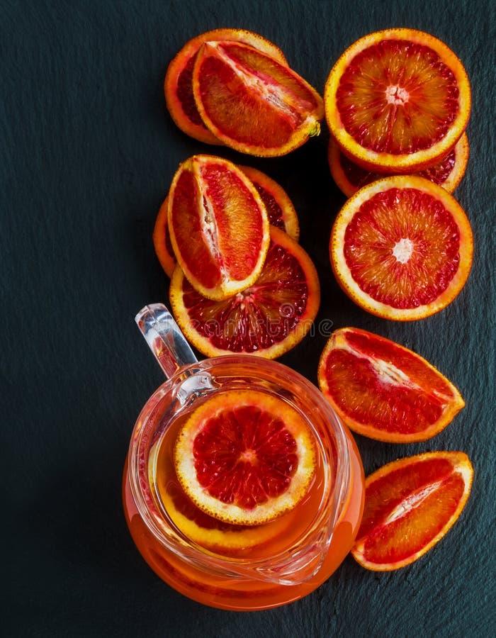 Skivad Sicilian röd apelsiner och orange fruktsaft i den glass tillbringaren på svart stenbakgrund Top beskådar royaltyfri foto