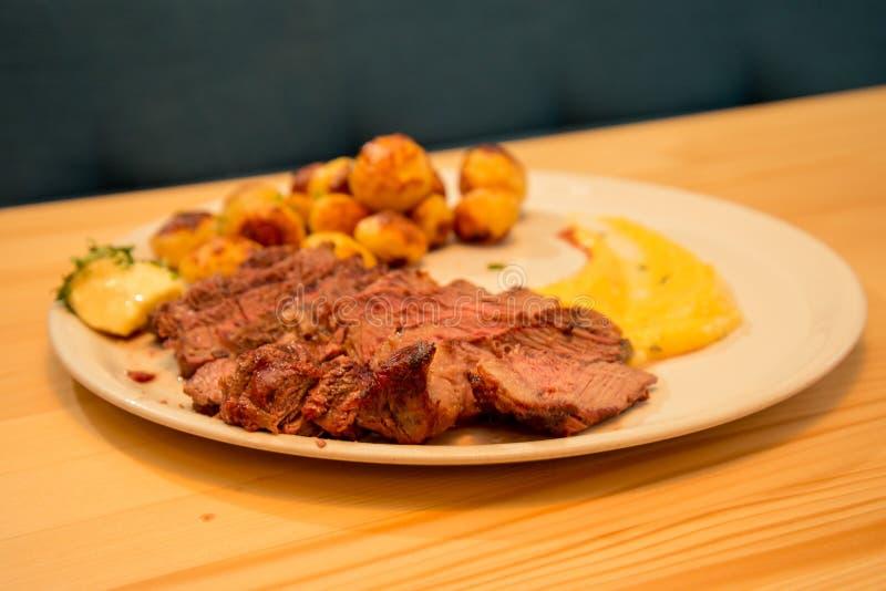 Skivad smaklig nötköttbiff med potatisen och sås arkivfoton