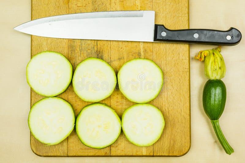 Skivad ung ny zucchini och kökkniv på skärbräda arkivbild
