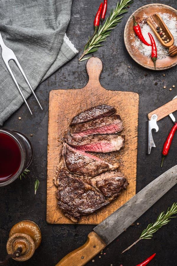 Skivad utmärkt medelsällsynt grillad nötköttgrillfeststek av fransyska på skärbräda på lantlig kökbakgrund med kniven, krydda arkivbilder