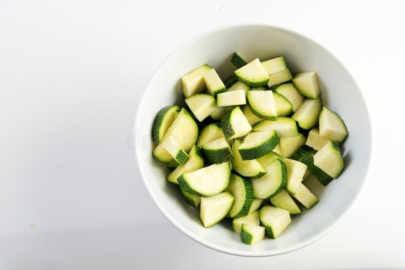 Skivad zucchini, förberedda grönsaker i en vit bunke på ett ljus royaltyfri fotografi