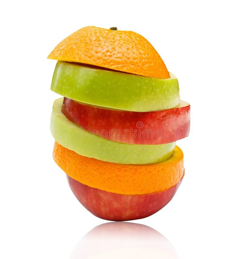 Skivade äpplen och orange frukt som isoleras på vit bakgrund royaltyfria bilder