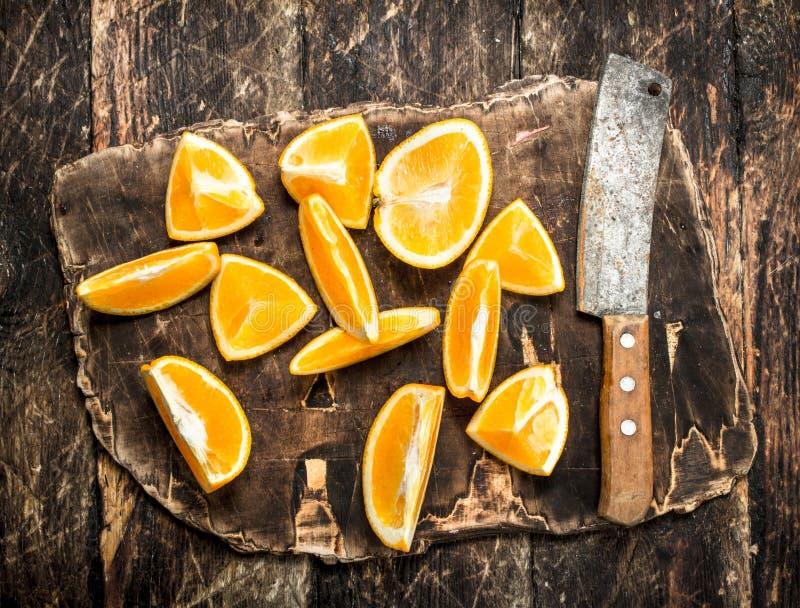 Skivade apelsiner med en handyxa på en skärbräda royaltyfri foto