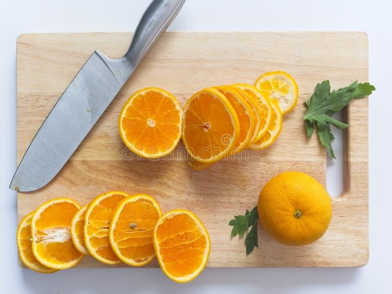 Skivade apelsiner på den ordnade träskärbrädan omkring royaltyfria bilder