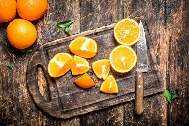 Skivade apelsinskivor på en skärbräda med en kniv fotografering för bildbyråer