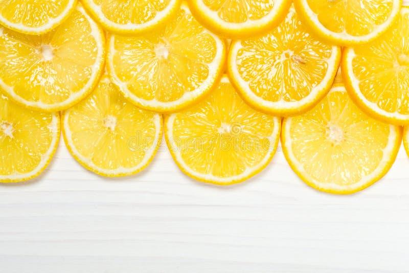 Skivade citroner på vit träyttersida arkivfoto
