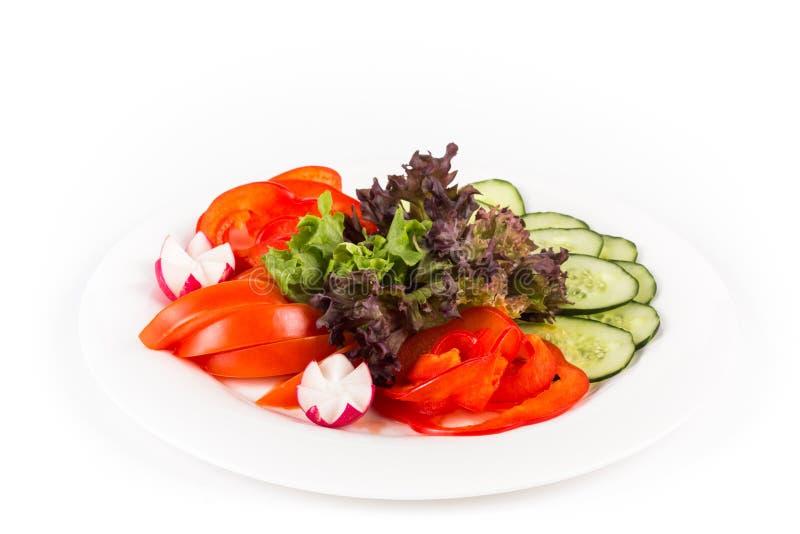 Skivade grönsaker på en platta På en vit bakgrund arkivfoton