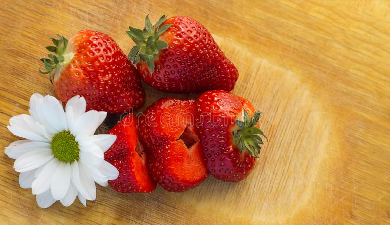 Skivade jordgubbar med blomman på en skärbräda arkivfoton