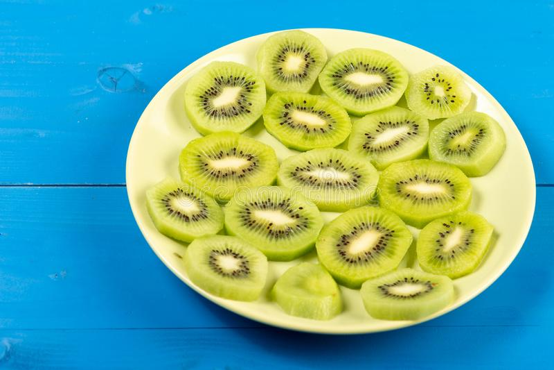 Skivade Kiwi Fruit On The Plate med blå tabellbakgrund royaltyfri foto