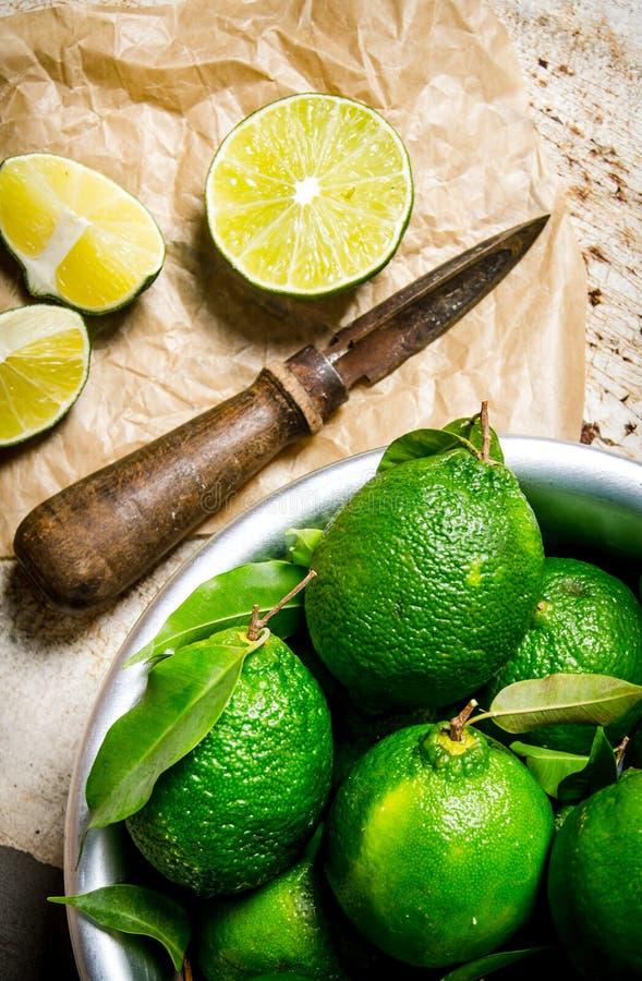 Skivade limefrukter med en kniv och en bunke På lantlig bakgrund royaltyfria bilder