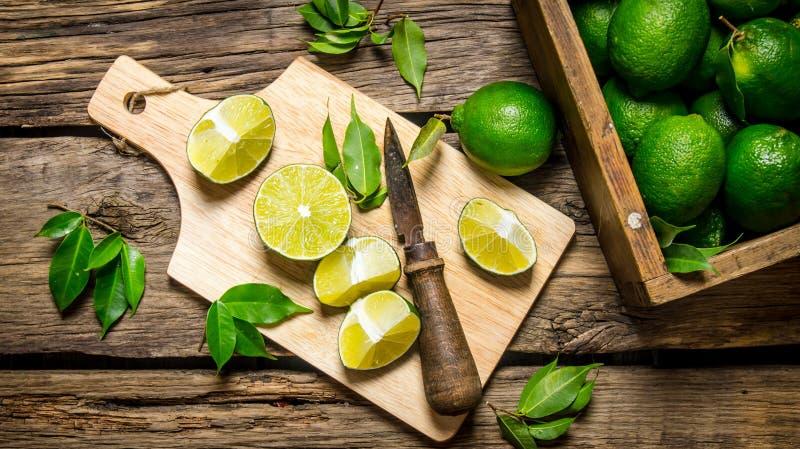 Skivade limefrukter på ett bräde med kniven och asken mycket arkivbild