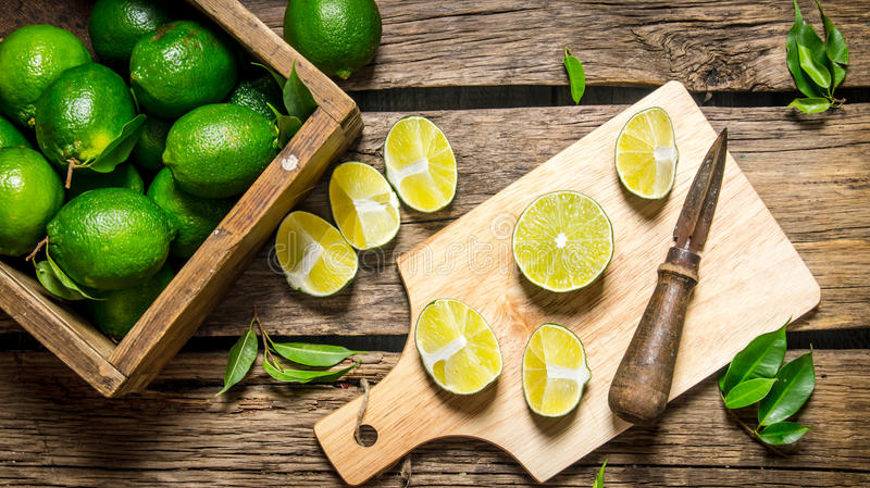 Skivade limefrukter på ett bräde med kniven och asken mycket arkivbilder