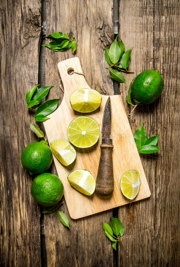Skivade limefrukter på ett träbräde med sidor och kniven arkivbild