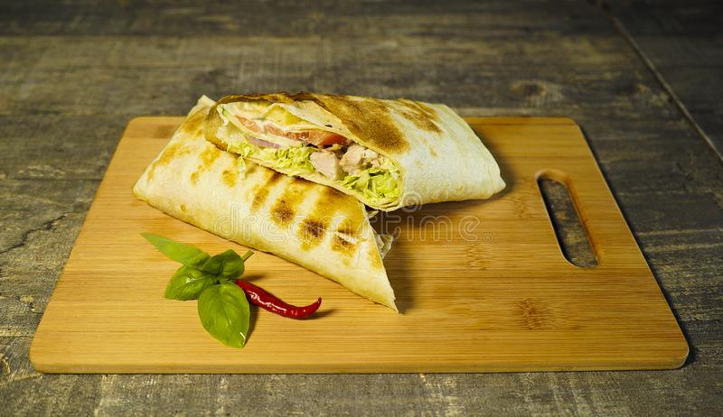 Skivade ny shawarma med peppar på en skärbräda royaltyfri fotografi