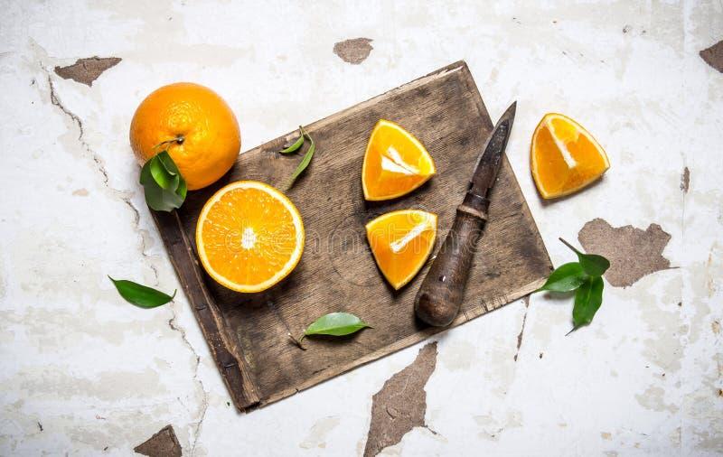 Skivade nya apelsiner på det gamla brädet royaltyfria bilder