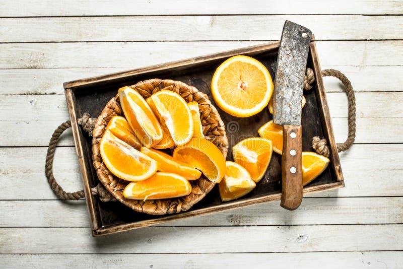 Skivade nya apelsiner på ett trämagasin fotografering för bildbyråer