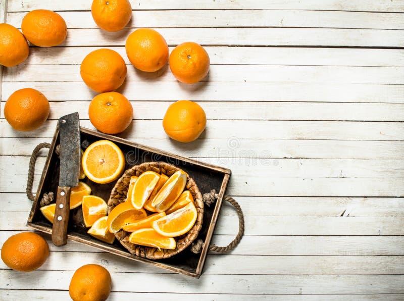 Skivade nya apelsiner på ett trämagasin royaltyfria bilder