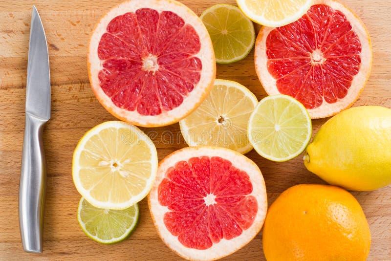 Skivade nya citrusa citroner, limefrukter, grapefrukter, apelsiner p? en tr?sk?rbr?da med en metallkniv, b?sta sikt royaltyfria foton