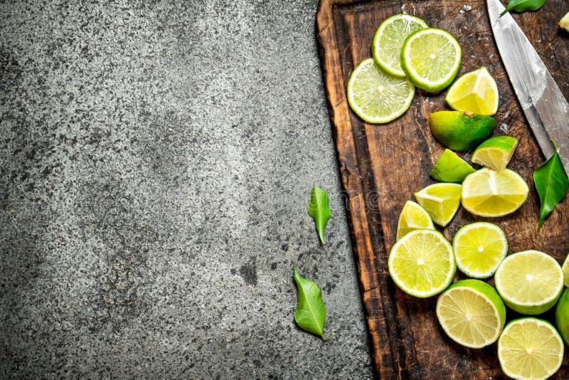 Skivade nya limefrukter på en skärbräda med en kniv royaltyfri bild