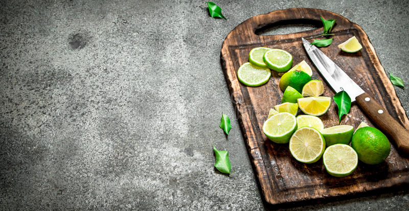 Skivade nya limefrukter på en skärbräda med en kniv royaltyfri fotografi