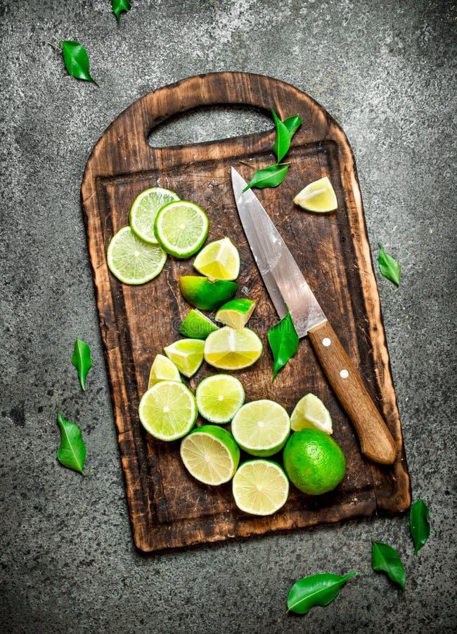 Skivade nya limefrukter på en skärbräda med en kniv royaltyfri foto
