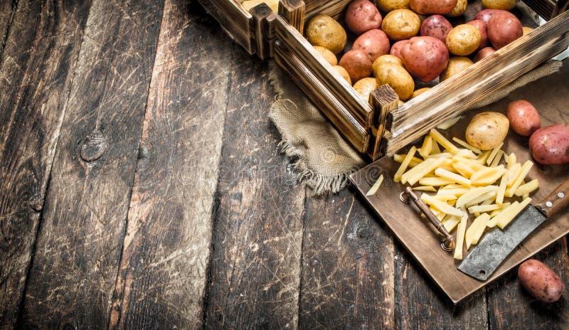 Skivade nya potatisar med en gammal handyxa arkivbild