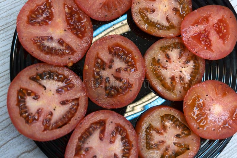 Skivade och hela körsbärsröda tomater för matbakgrund, persilja, havet som är salt som är svart och rosa färger peppra på en mörk royaltyfria bilder
