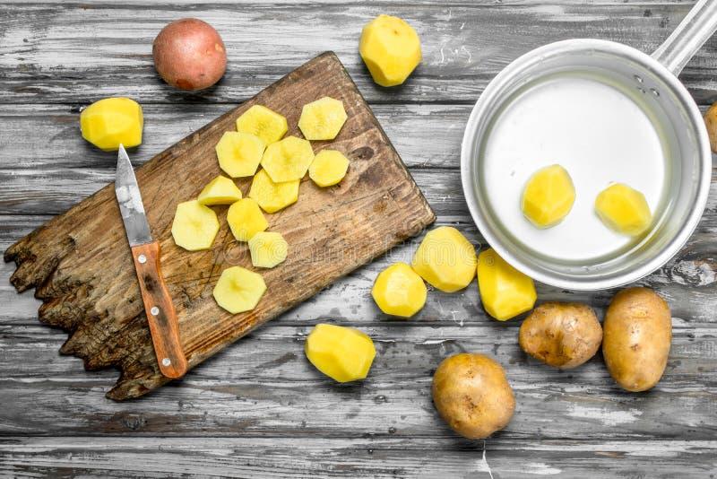 Skivade potatisar på en skärbräda med en kniv och skalade potatisar i en kastrull royaltyfria foton