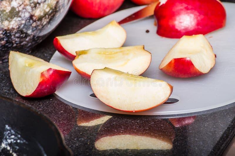 Skivade röda äpplen på skärbräda arkivfoton
