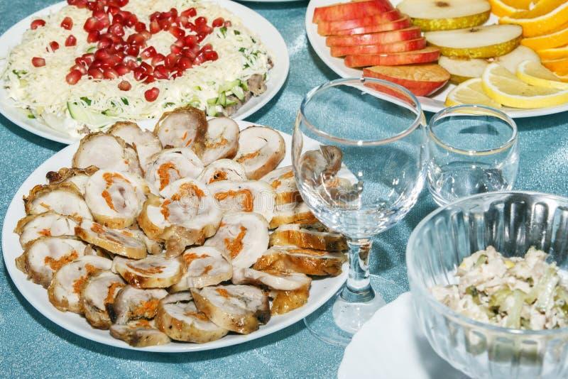 Skivade rullar från höna- eller kalkonkött som är välfyllt med grönsaker på banketttabellen Grönsak- och fruktsallad, skivat äppl royaltyfria foton