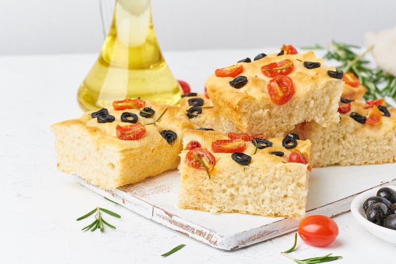 Skivade stycken av focaccia med tomater, oliv och rosmarin Kopiera utrymme f?r text Traditionellt italienskt plant br?d Slapp fok royaltyfri foto