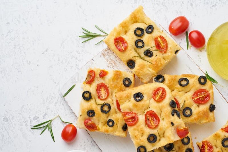 Skivade stycken av focaccia med tomater, oliv och rosmarin Kopiera utrymme f?r text Traditionellt italienskt plant br?d Top besk? arkivbild