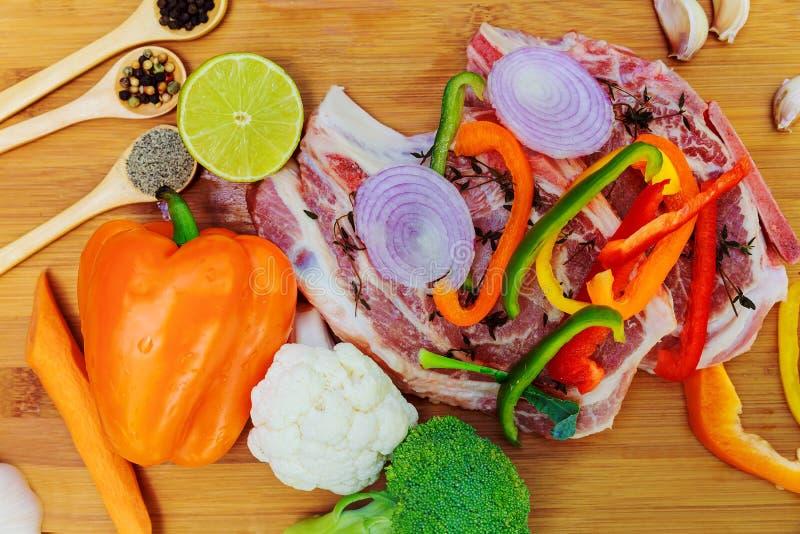 Skivade stycken av rått kött för grillfest på träyttersida, menymatlagningrecept Mat biff, nötköttbbq, tomater, peppar, kryddor royaltyfri bild