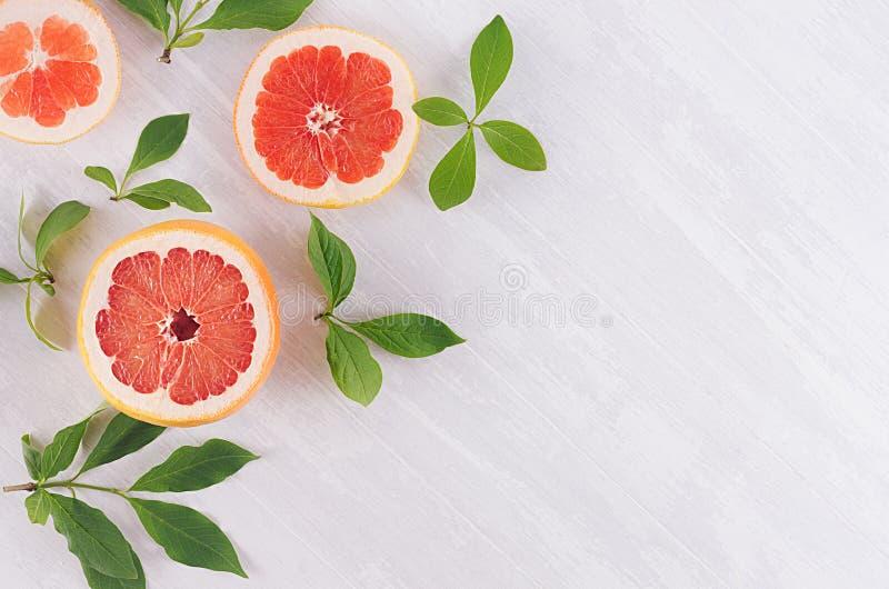 Skivagrapefrukt- och gräsplansidor på mjuk vit träbakgrund, modell, bästa sikt, closeup royaltyfri fotografi