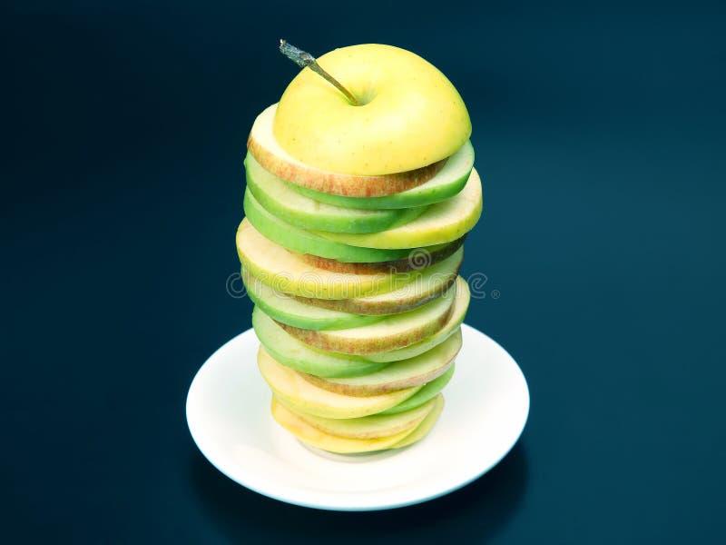 Skivat äpple för ‹för †i en pyramid på en vit platta arkivbild