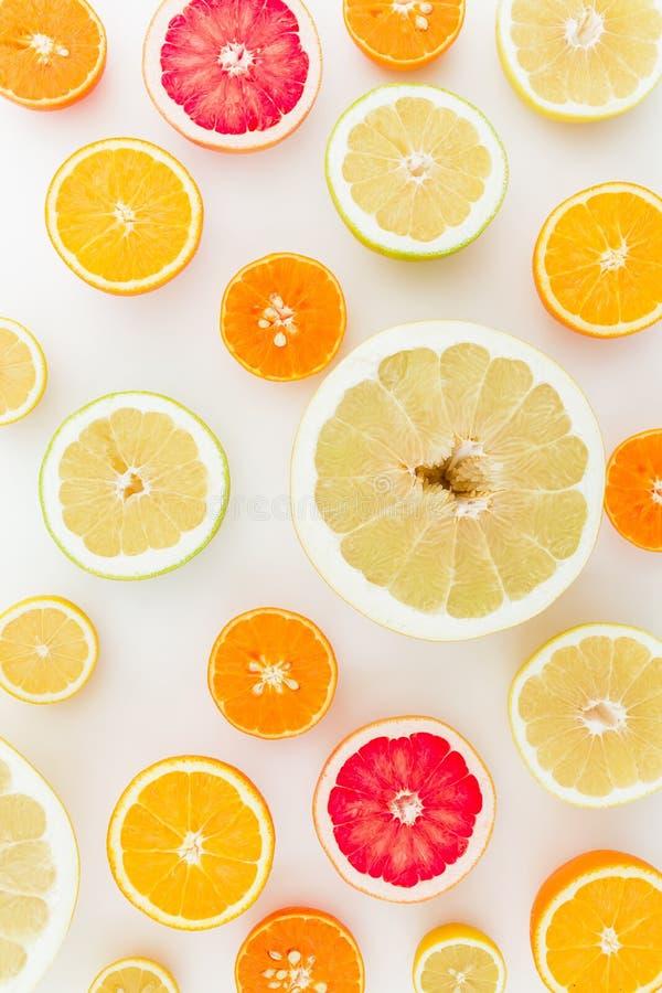 Skivat av smakliga citrusfrukter på vit bakgrund Lekmanna- lägenhet, bästa sikt royaltyfri fotografi