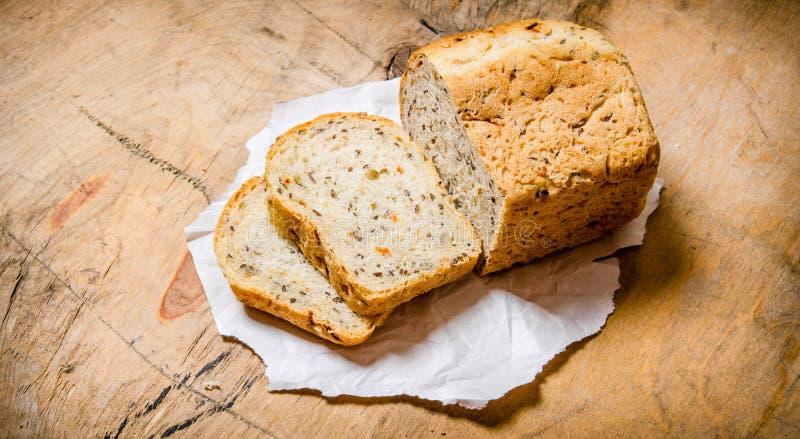 Skivat bröd på papper trägrund tabell för djupfält royaltyfri foto