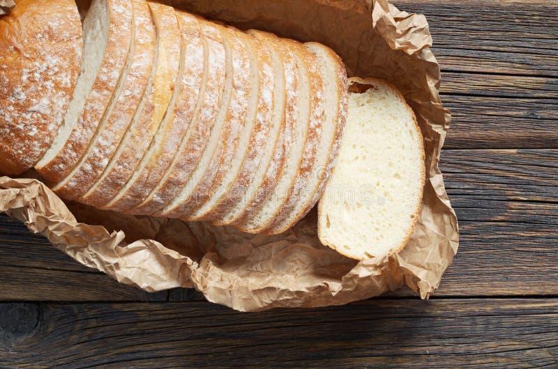 Skivat bröd på skrynkligt papper arkivfoto