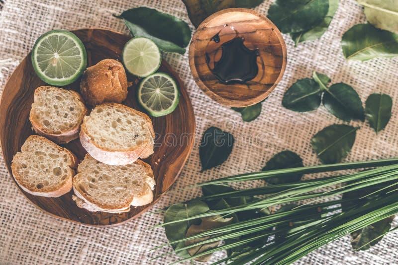 Skivat bröd på trätabellen med ny och grön limefrukt fotografering för bildbyråer