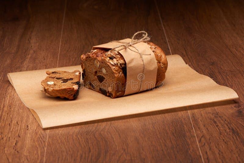 Skivat fruktbröd med russin, katrinplommoner och muttrar i bakning skyler över brister på den mörka trätabellen arkivfoto