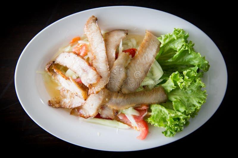 Skivat griskött grillade thailändsk stil med grön sallad på den vita plattan royaltyfri fotografi