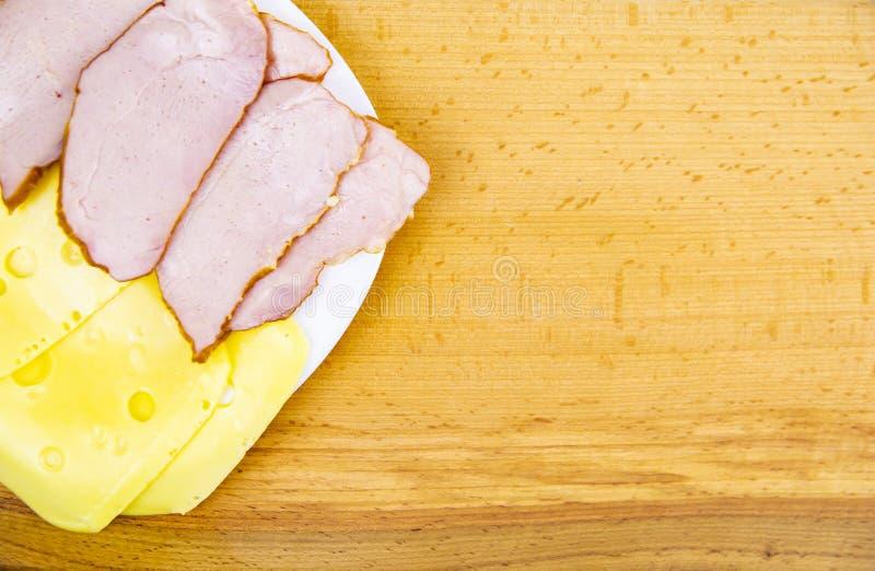 Skivat hårdost och kött på en träskärbräda royaltyfri bild