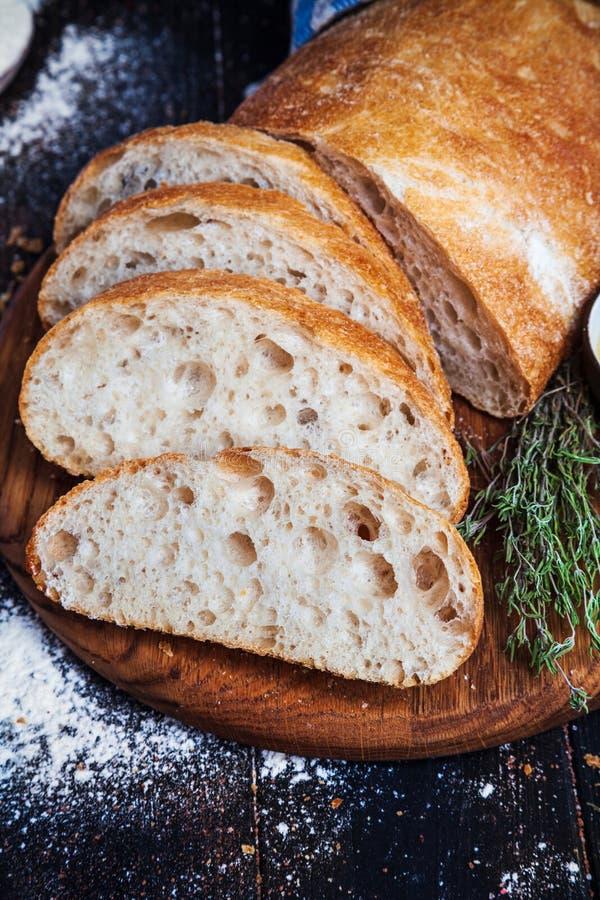 Skivat hemlagat italienskt ciabattabröd med olivolja på mörk bakgrund Ciabatta örter, olivolja, mjöl Övre sikt för slut, kopia s arkivfoto