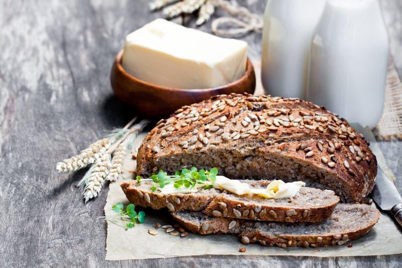 Skivat hemlagat rågbröd på bakningpapper och flaskor av mjölkar nolla royaltyfria foton