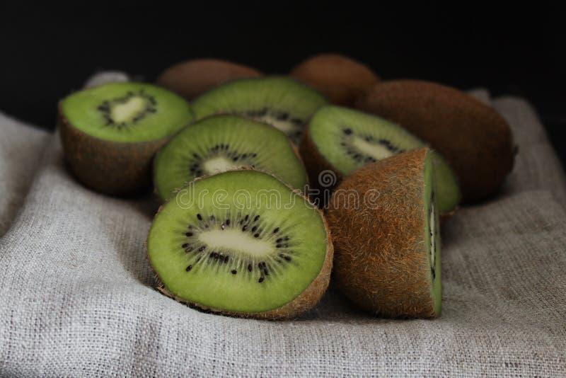 Skivat kiwislut upp grön frukt, mörk bakgrund arkivbild