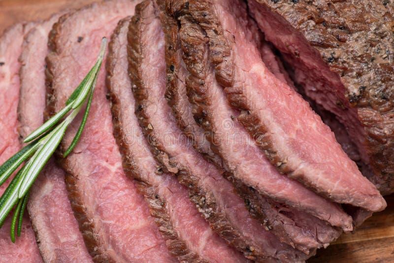 Skivat nötkött för stek för gräsFed saftigt havre som garneras med tomater, nya Rosemary Herb och regnbågepepparkorn royaltyfri foto